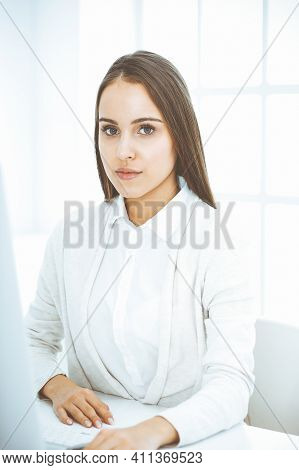 Young Cheerful Woman Sitting At The Desk With Computer And Looking At Camera In White Colored Office