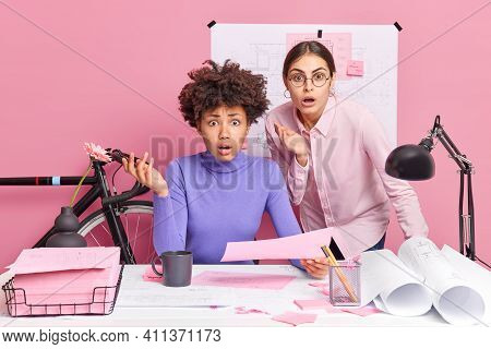 Photo Of Puzzled Two Female Coworkers Stare Indignant At Camera Realise About Deadlie Have Not Much