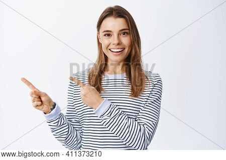 Portrait Of Smiling Caucasian Woman With Blond Hair, Showing Good Deal Offer, Pointing Fingers Left