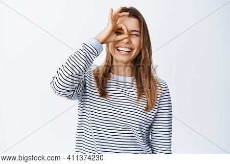 Happy Young Woman Feeling Alright, Showing Ok Sign Over Eye, Making Okay Gesture And Smiling Satisfi