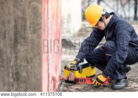 Asian Maintenance Worker Man With Red Aluminium Spirit Level And Tool Box Checking Valve Of Old Wate