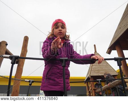 Girl 7 Years Old On The Playground. The Child Is Dressed In Warm Demi-season Clothes - A Purple Jack