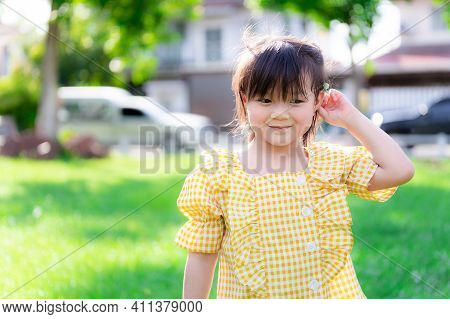 Happy Girl Tucked A Flower From The Grass To Her Ear. Cute Kids Play With Nature In The White Lawn I