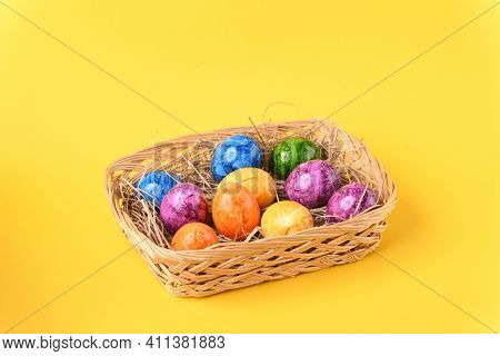 Colorful Easter Eggs In The Basket On The Yellow Background.
