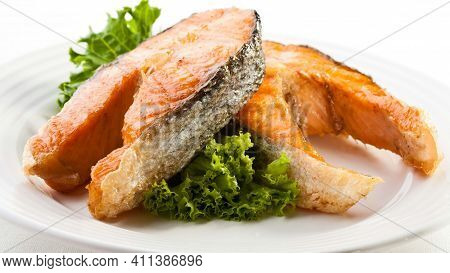 fried fish in with plate with white table slices and pieces of fish with green leaves grilled fish tasty and delicious food seafood