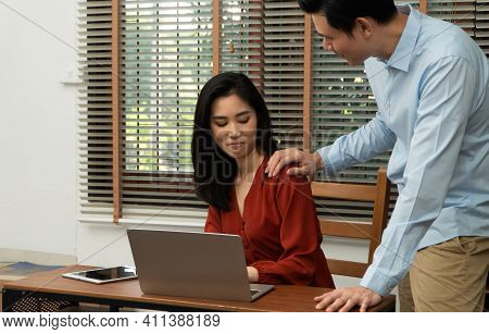 Boss Touching Shoulder Of A Young Female Employee In Office At Workplace. She Is Uncomfortable And A