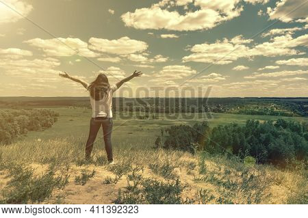 Young Woman Standing In A Wheat Field With Sunrise On The Background. A View From The Back Of A Wome