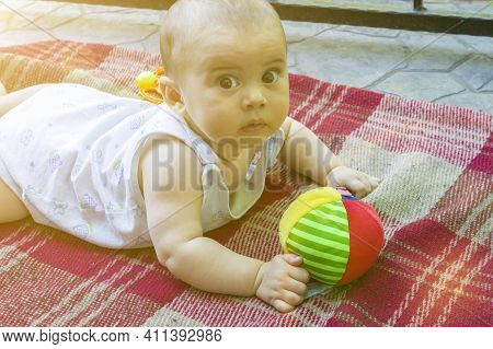 Adorable Baby Boy Learning To Crawl And Playing With Colorful Rainbow Ball Toy. Cute Laughing Child