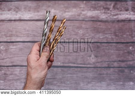Close-up Drill Bits In Hand. The Smeared Hand Of A Worker With Drill Bits. Lettering