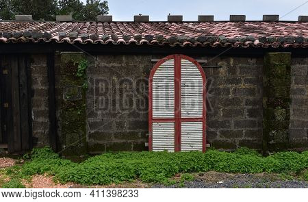Unusual White And Red Shutters On A Chicken Coop In The Azores.