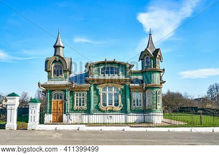 Stylish Green Vintage Log Building With Spires On Towers And Decorated Windows On Village Street Und