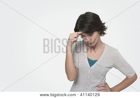 Tensed woman standing with head in hand on white background