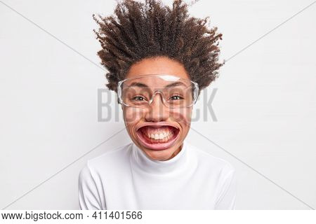 Portrait Of Funny Positive Dark Skinned Woman Smiles With Teeth Has Big Mouh Poses Under Air Pressur