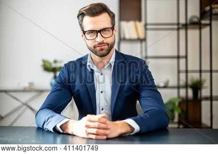 Successful Handsome Businessman Sitting At Desk, Talking At Camera, Sharing Experience And Ideas, Fr