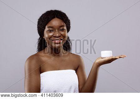 Skin Care. Happy Attractive Black Lady Holding White Jar With Moisturising Cream On Palm, Demonstrat