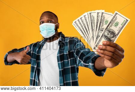 Rich African Man Holding Money Cash Gesturing Thumbs Up Posing Wearing Protective Face Mask For Covi