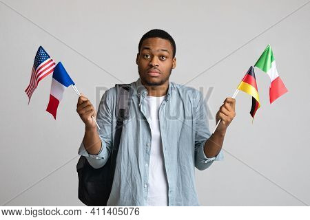 Confused Black Guy With Backpack And Bunch Of Flags Of Different Countries Posing On Grey Studio Bac
