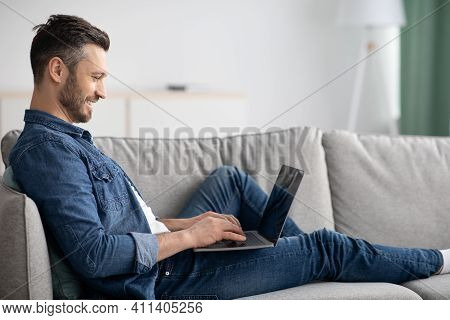 Side View Of Middle-aged Man Reclining On Couch In Living Room, Using Newest Laptop, Copy Space. Hap
