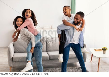 Happy Loving Family. Cheerful African American Man And Woman Having Fun With Children In Living Room