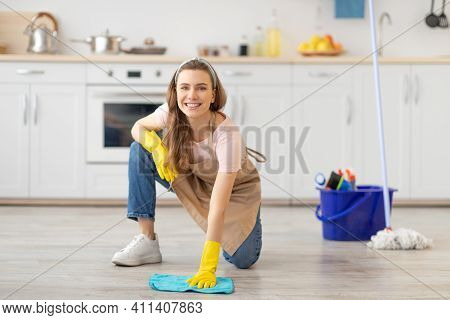 House Keeping Concept. Happy Young Woman Wiping Floor In Kitchen, Wearing Rubber Gloves, Using Clean