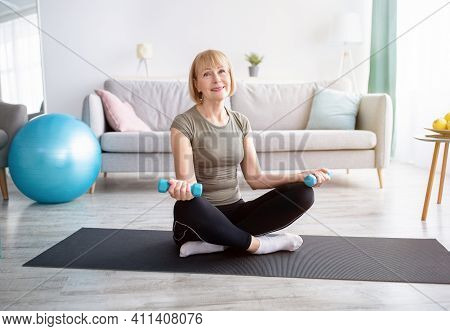 Positive Mature Woman In Sports Clothes Doing Strength Exercises With Dumbbells At Home, Free Space.