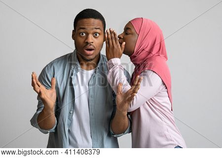 African-american Young Woman In Hijab Sharing Secret Or Whispering Gossips Into Her Boyfriends Ear,