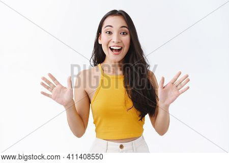 Happy, Fascinated Good-looking Stylish Modern Asian Woman In Yellow Top, Raise Hands Sideways And Sm