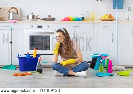 Unhappy Millennial Housemaid Sitting On Kitchen Floor With Heaps Of Supplies, Sick And Tired Of Clea