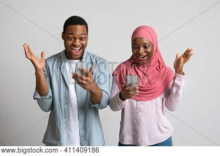 Amazed Muslim African American Man And Woman In Hijab Using Smartphones, Grey Studio Background. Emo