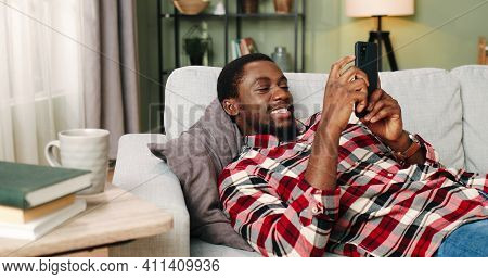 Side View Of African American Handsome Young Man Smiling Cheering Up Watching Video Or Film Online W