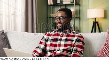 Portrait Of Cheerful Smiling African American Young Man In Glasses Speaking On Video Chat On Laptop