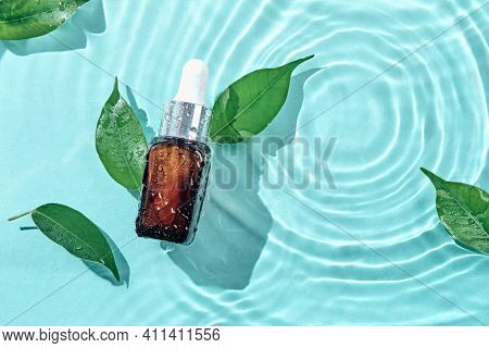Beauty Cosmetic Lotion Serum Bottle And Green Leaves On Water Concentric Circles Background. Treatme
