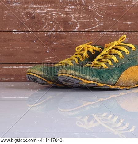 Clothes Shoes And Accessories - Closeup Old Pair Green And Yellow Sneakers Wooden Background With Re