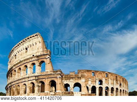 Rome, Italy. Arches Archictecture Of Colosseum (colosseo) Exterior With Blue Sky Background And Clou