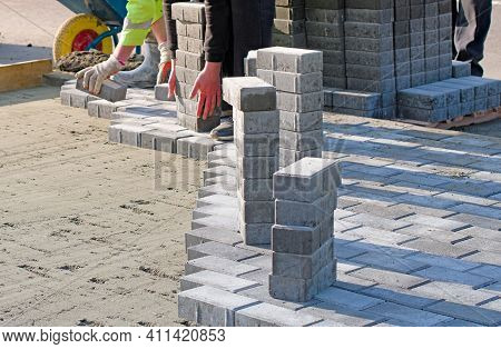 The Master In Gloves Lays Paving Stones In Layers. Garden Brick Pathway Paving By Professional Paver
