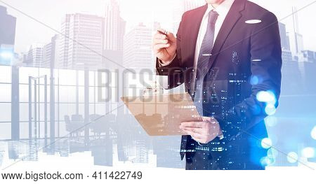 Businessman With Clipboard And Toned Office Interior, Skyscrapers With Lights. City Buildings And Co