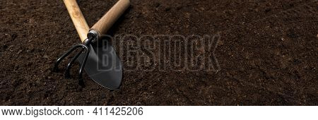 Garden Tool On The Ground For Planting Plants. Garden Background. Banner Poster With Space For Text.