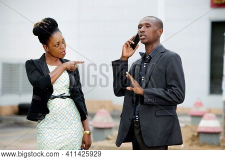 Woman Having A Serious Argument Against A Businessman Talking On The Phone Outdoors