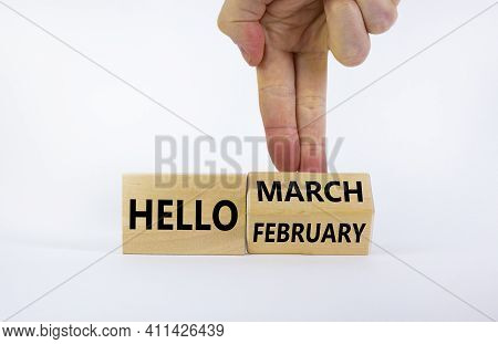 Symbol For The Change From February To March. Businessman Turns Wooden Cubes And Changes Words 'hell