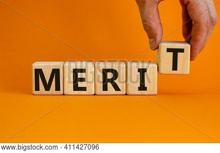 Merit Symbol. Wooden Cubes With The Word 'merit'. Businessman Hand. Beautiful Orange Background, Cop