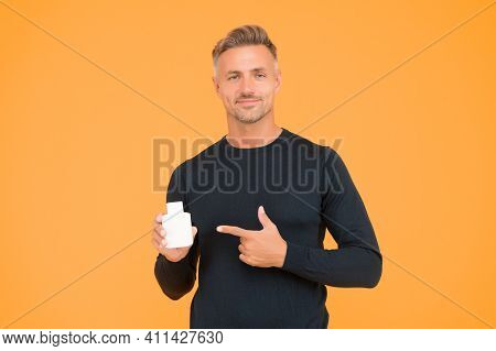 Choosing Right Scent For You. Handsome Man Point Finger At Perfume Bottle Yellow Background. Adverti
