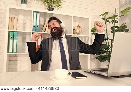 Inspiring Music For Success. Happy Businessman Listen To Music In Office. Manager Celebrate Success.