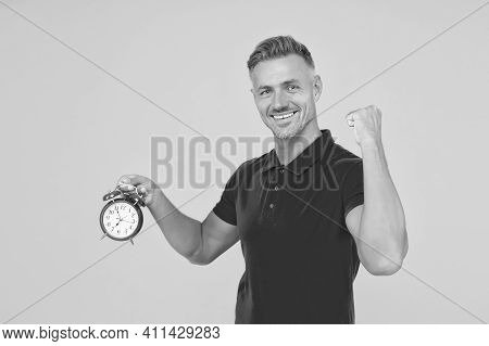 Happy Caucasian Guy Flex Strong Arm Holding Alarm Clock Yellow Background, Punctuality.