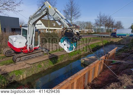 Construction Workers Are Placing Anchors For A Wooden Retaining Wall For A Garden Along A Canal