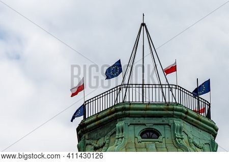 Wroclaw, Poland - May 03 2020: Top Of Old Tenement House With Polish Flags And European Union Flags