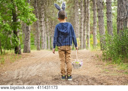A Child Looking For Easter Eggs In The Forest. Little Boy Hunting For Easter Egg In Spring Wood On E