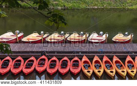 Wroclaw, Poland - May 03 2020: Row Of Kayaks And Motorboats Near Wooden Bridge