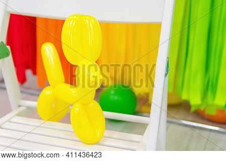 Close-up And Selective Focus Of Yellow Balloon In Form Of Dog On Multicolored Background On White Ch