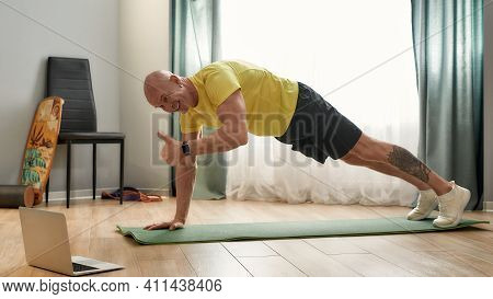 Athletic Man Exercising At Home On A Sporting Mat. Male Trainer Conducting Online Lesson And Showing