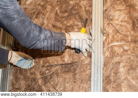 The Worker Attaches Mineral Wool To The Walls For Further Plasterboard Cladding. Thermal Insulation